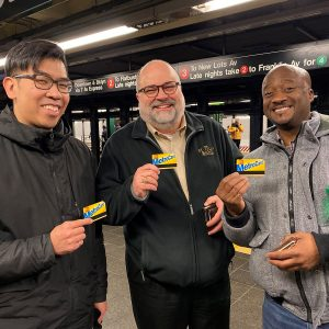 Three men stand together, smiling and holding metro cards