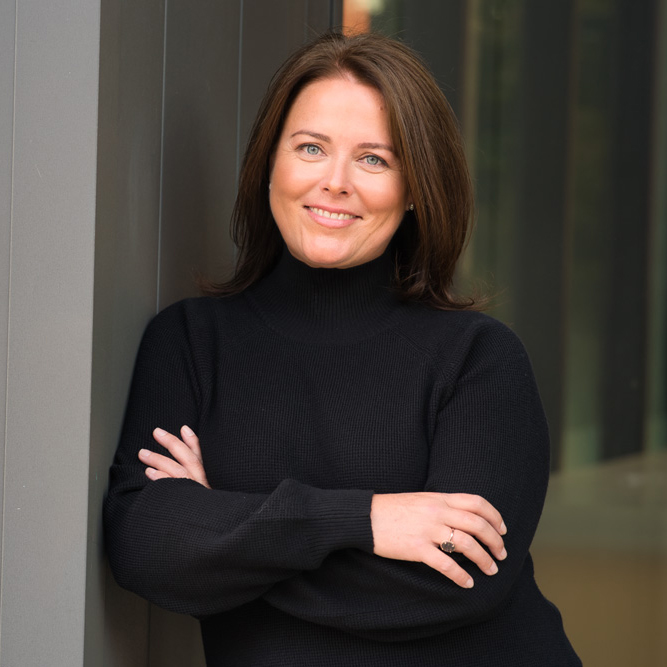 Kim Emmerson. A woman with dark hair wearing a black turtleneck stands with her arms crossed, smiling.