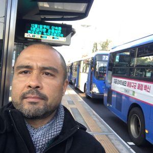 A selfie of a man at a bus stop