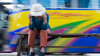 A woman sits on a bench bent over and holding her hat onto her head while a fast bus goes by.