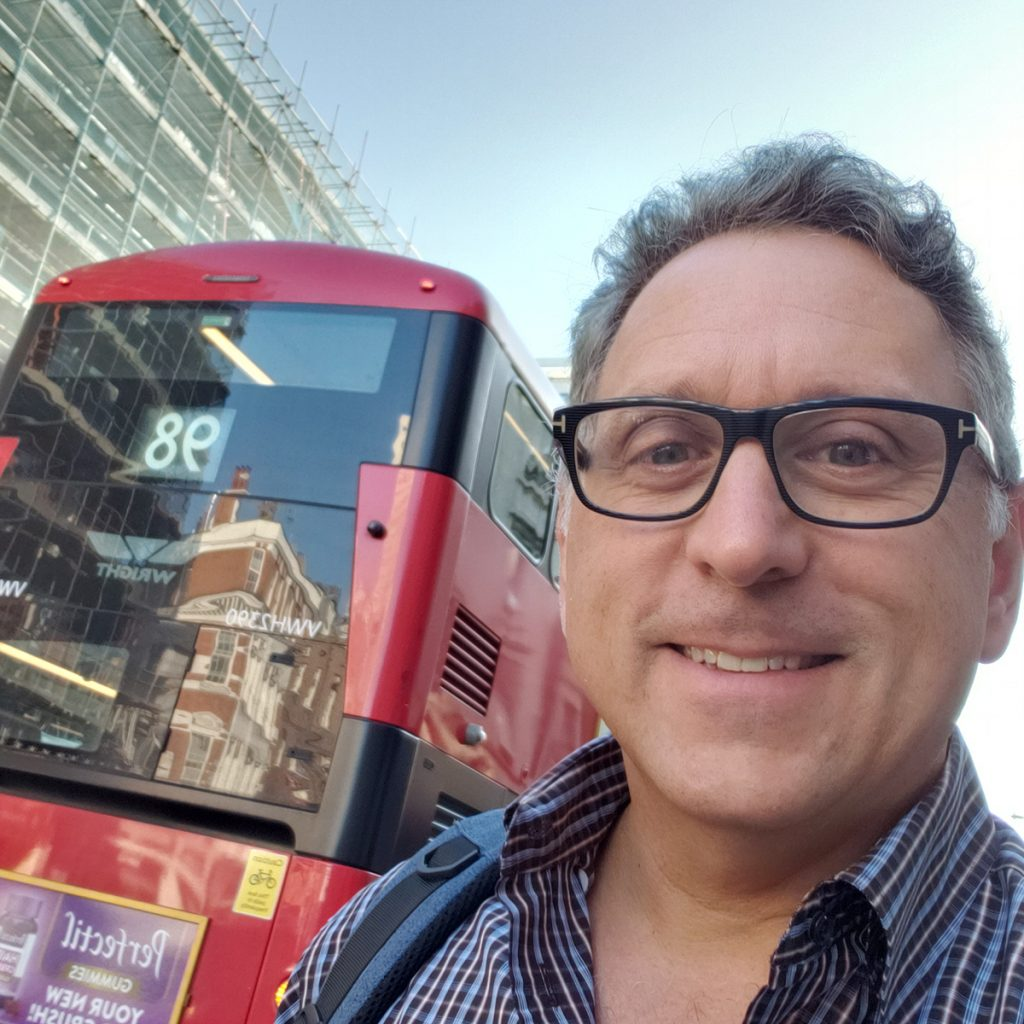 A selfie of a man in front of a doubledecker bus in London