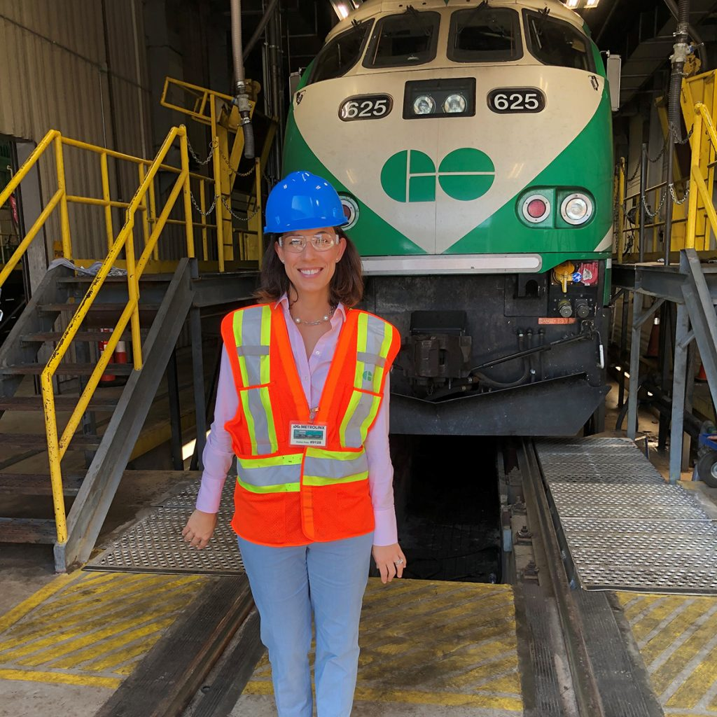 A woman stands in front of a subway car while wearing a hardhat and safety vest
