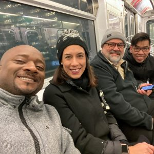 A group of smiling people sit on a subway