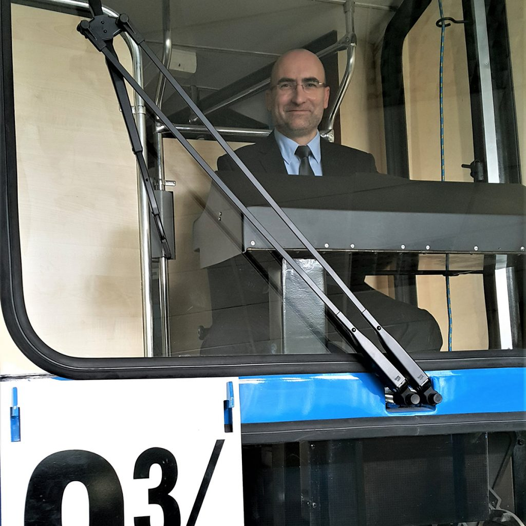 A man smiles from a bus that reads