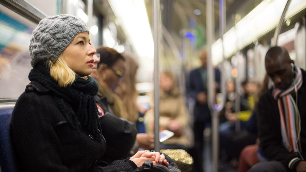 Woman in winter coat riding on metro during rush hour