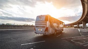 A doubledecker bus travels down a highway