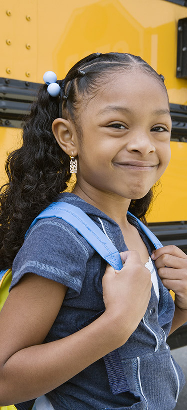 A woman smiles in front of a yellow school bus.