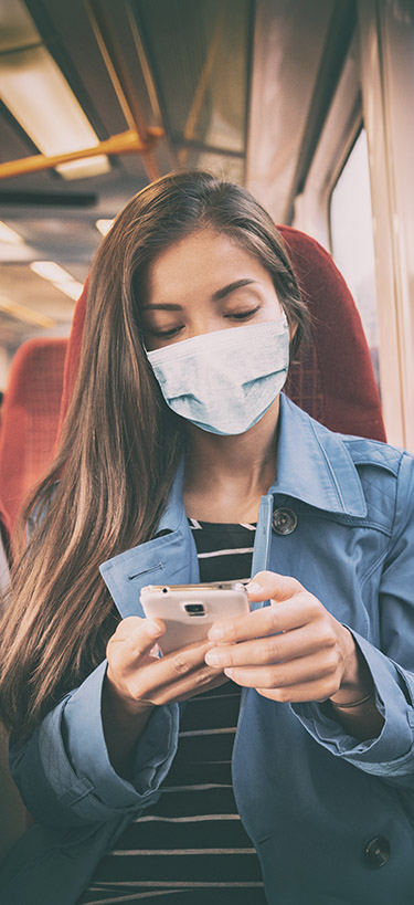 A woman sits on a bus wearing a face mask and looking at her phone.