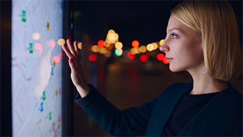 A white, blonde woman touches a large touchscreen map