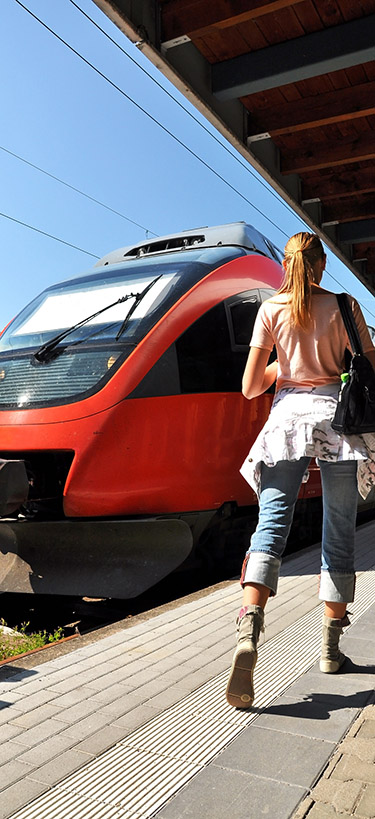 A woman waits in front of a red train.